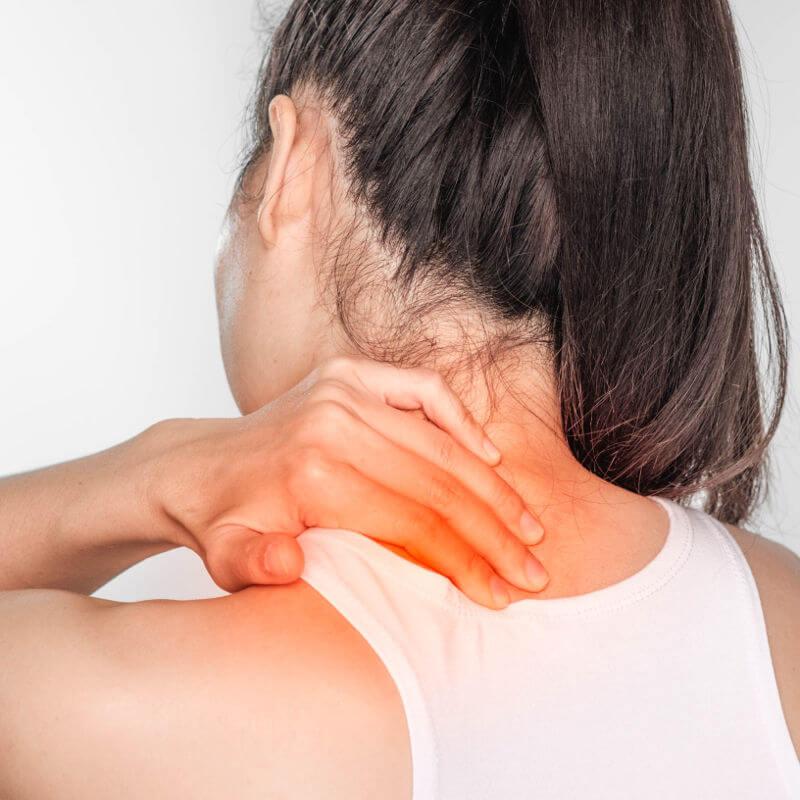 Frau hält sich mit Schmerzen den steifen Nacken