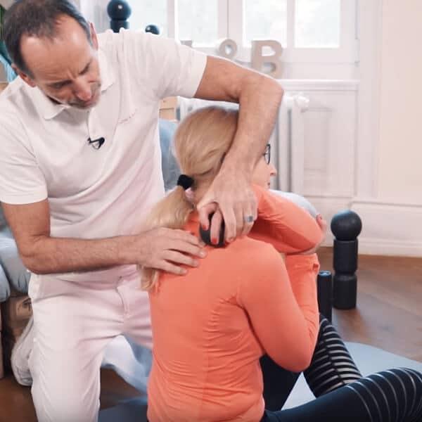 Roland Liebscher-Bracht zeigt einer Frau eine Übung. Sie rollt sich mit der Mini-Kugel den Schulter- und Nackenbereich.