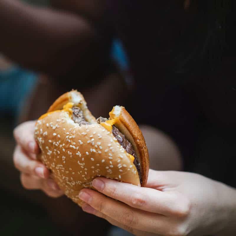 Person hält einen Burger in der Hand