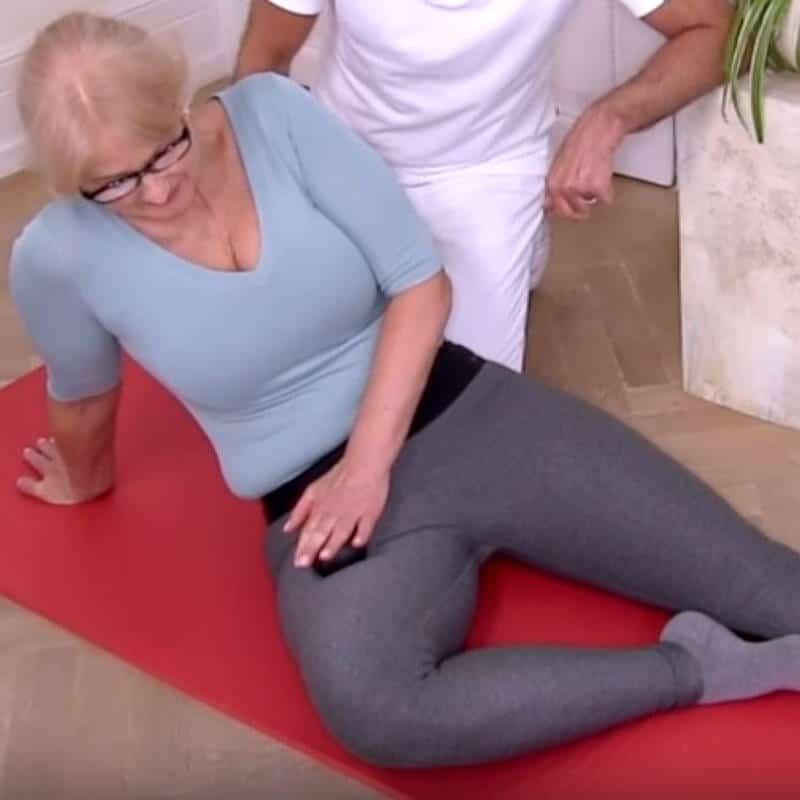 Patientin rollt mit Minikugel über Muskel im Oberschenkel, der das Wirbelgleiten auslöst