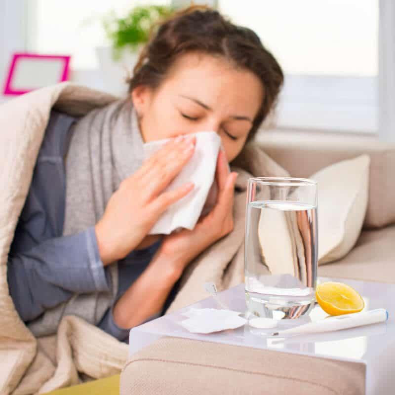 Eine Frau mit verschnupfter Nase im Bett, vor ihr Wasser, Zitrone, Fiberthermometer und Medikamente auf einem Nachtschrank