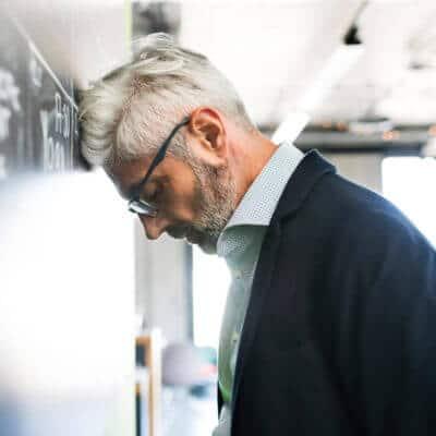 Geschäftsmann lehnt seinen Kopf erschöpft gegen eine Tafel