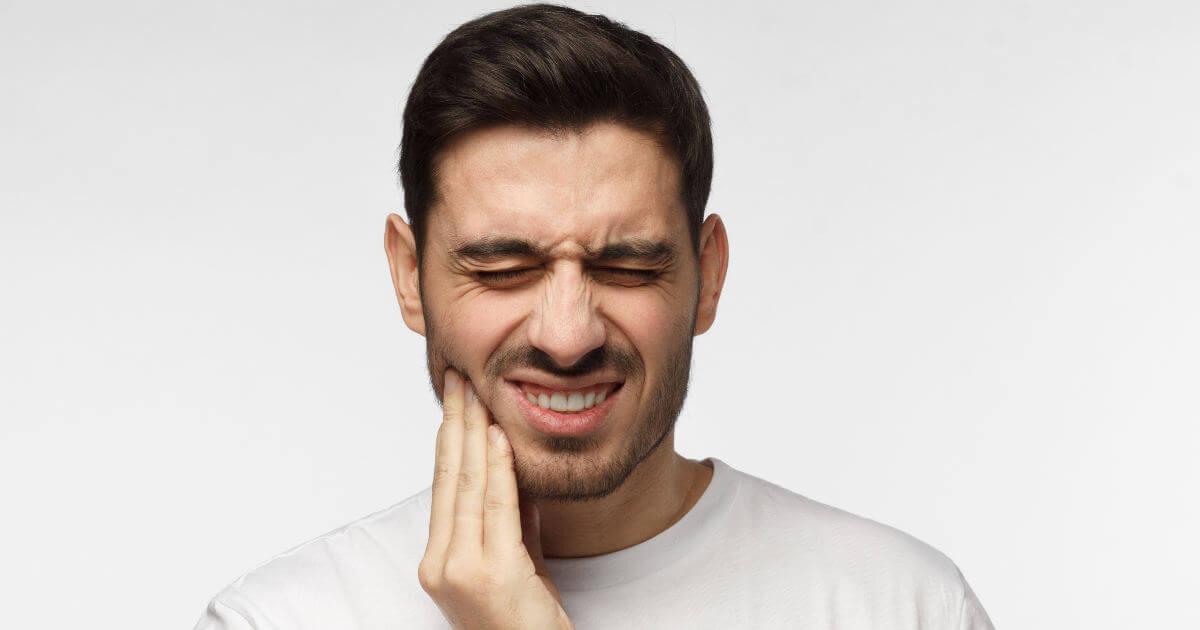 Mann hält sich den Kiefer und verzieht das Gesicht vor Schmerzen