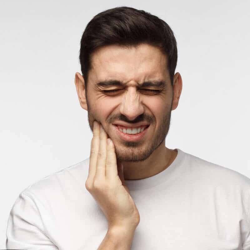 Mann hält sich mit der rechten Hand den Kiefer und zieht schmerzverzerrtes Gesicht