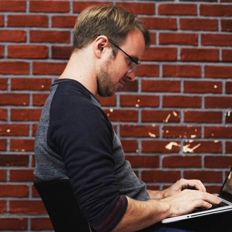 Ein Mann sitzt mit einem Laptop auf dem Schoß