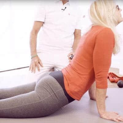 Unter Anleitung von Schmerzspezialist Roland Liebscher-Bracht dehnt eine Patientin ihren rückseitigen Körperbereich gegen Gliederschmerzen