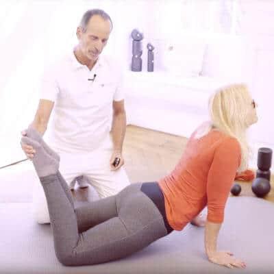 Mit Unterstützung von Schmerzspezialist Roland Liebscher-Bracht dehnt eine Patientin ihren rückseitigen Körperbereich gegen Gliederschmerzen