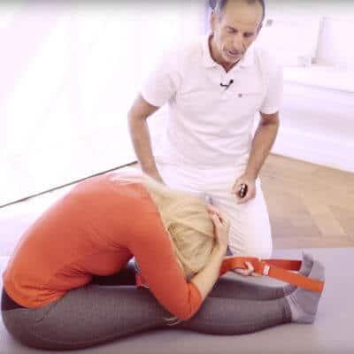 Unter Anleitung von Schmerzspezialist Roland Liebscher-Bracht dehnt eine Patientin mithilfe der Übungsschlaufe ihren vorderen Körperbereich gegen Gliederschmerzen
