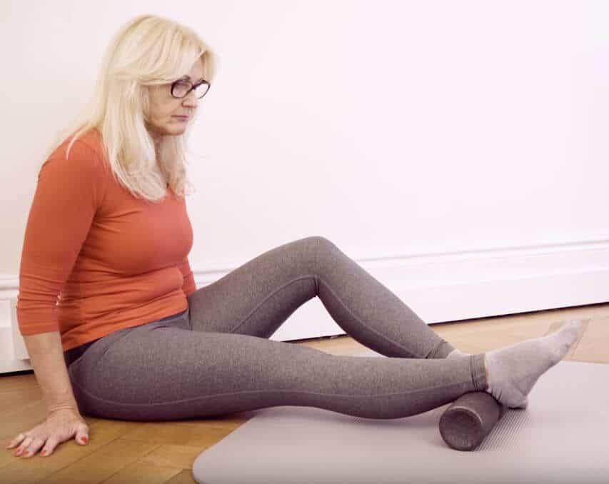 Eine Frau rollt mit der Medi-Faszienrolle den unteren Teil ihrer Wade bei Achillessehnenschmerzen und Hammerzehen