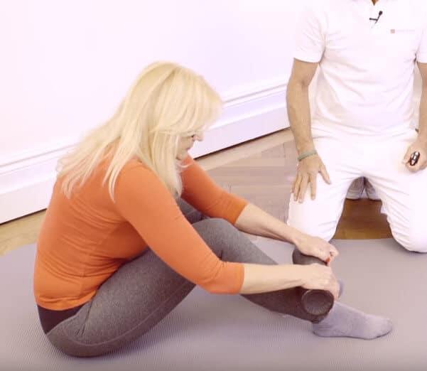 Frau nutzt Medie-Faszienrolle an den Beinen