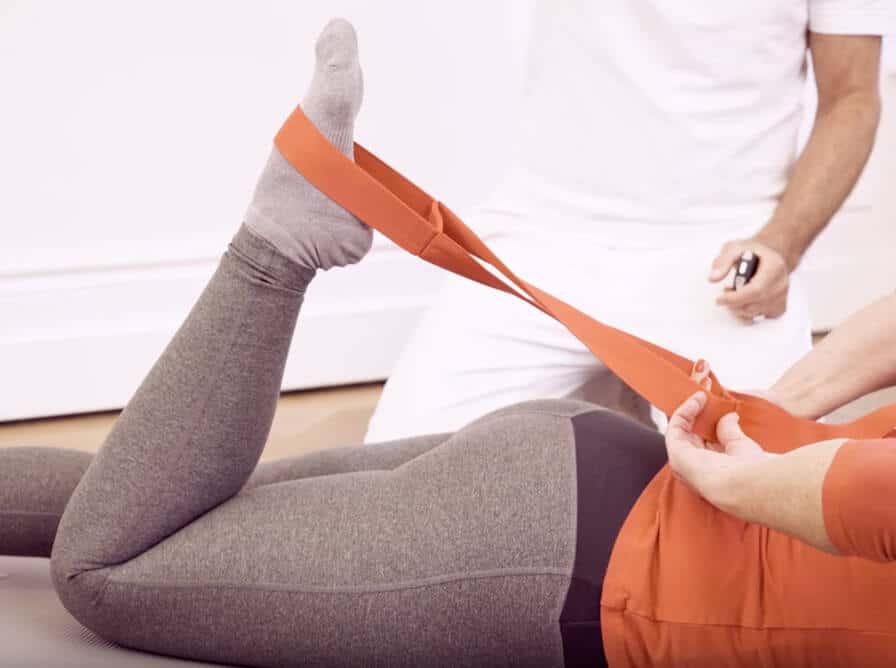 Eine Frau liegt bäuchlings und zieht ihre Wade mithilfe der Übungsschlaufe in Richtung Gesäß. Die Schlaufe ist um ihren Fuß gelegt und sie zieht mit beiden Händen über den Rücken an der Schlaufe. Der Oberschenkel bleibt auf dem Boden liegen.