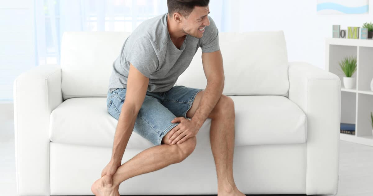 Mann sitzt auf dem Sofa und hält sich vor Schmerzen das Bein