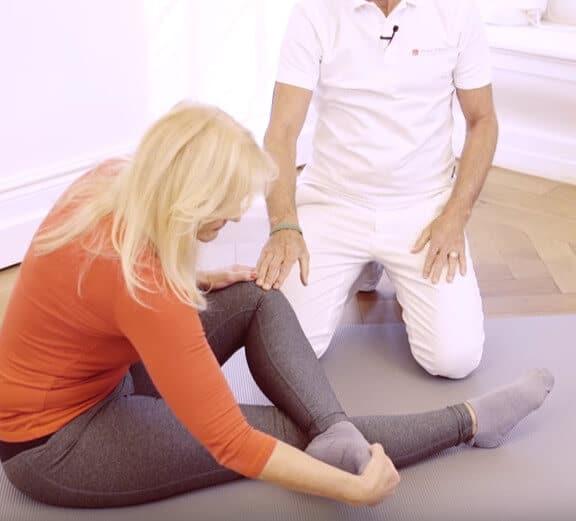 Frau dehnt sich den Fuß aufgrund eines Hammerzehs. Sie sitzt auf einer Übungs-Matte, ihr linkes Bein ist über das rechte geschlagen und sie zieht die Zehen des linken Fußes mihilfe der rechten Hand in die Beugung. Diese Übung hilft auch bei Beschwerden mit dem Spreizfuß.