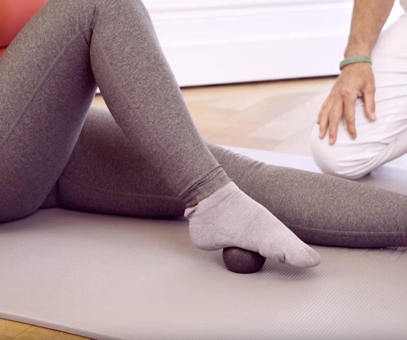 Frau rollt mit dem Fuß über die Mini-Kugel