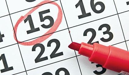 Es ist ein Kalender mit den Zahlen wie 15,16, 22 und 23 zu sehen. Die Zahl 15 ist mit einem roten Kreis eingekreist und rechts darauf liegt ein roten Marker ohne Deckel.