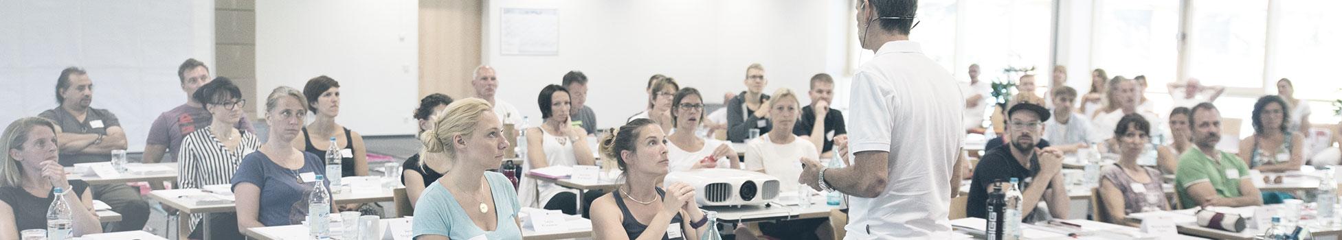 In einem Seminarraum hören viele Personen (vornehmlich Frauen) dem Vortragenden aufmerksam zu.