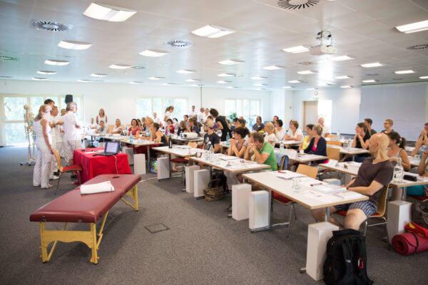 Aufnahme von Seminarraum zur Liebscher & Bracht Ausbildung mit vielen Teilnehmern, die dem Dozenten zuhören.