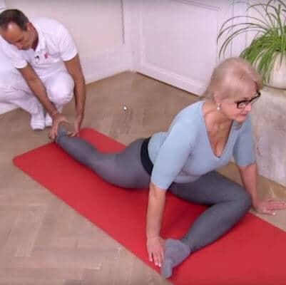Patientin führt Engpassdehnung gegen Schmerzen in der Lendenwirbelsäule aus. Roland Liebscher-Bracht verhilft ihr bei der Ausführung