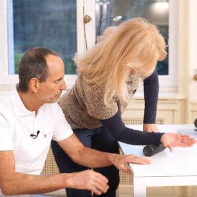 Schmerzspezialist Roland Liebscher-Bracht zeigt einer Patientin eine Faszien-Rollmassage für den Handrücken gegen Schmerzen im Handgelenk