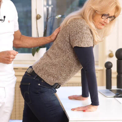Eine Patientin führt eine Dehnübung des Handgelenks durch, um ihre Schmerzen im Handgelenk zu lindern