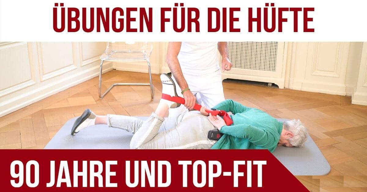 """Bild mit Überschrift """"Übungen für die Hüfte"""" und unten steht """"90 Jahre und Top-Fit"""". In der Bildmitte liegt ein alte Frau auf dem Bauch und mach mithilfe eines Mannes eine Übung fürs Knie mit der Übungsschlaufe - heranziehen des Beines an den Po"""
