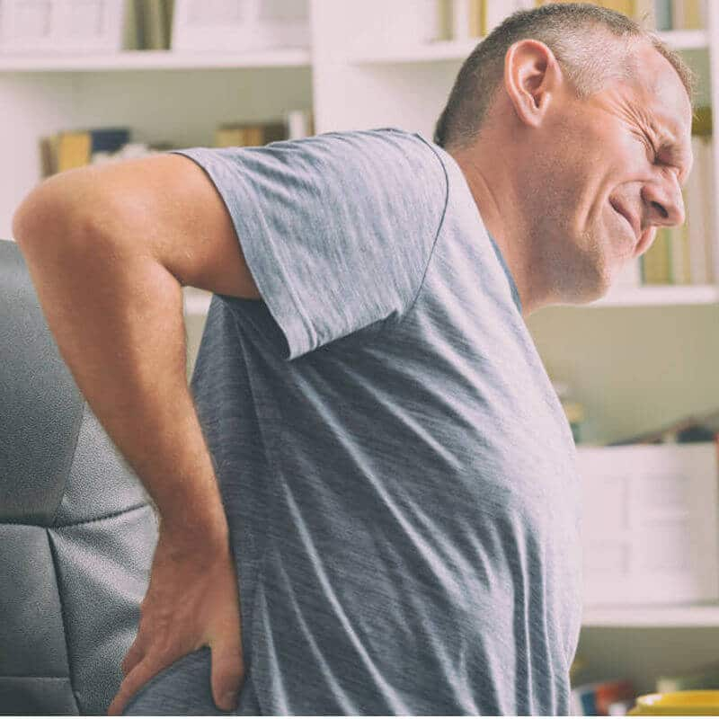 Mann sitzt auf einem Bürostuhl und hält sich seine schmerzende Lendenwirbelsäule