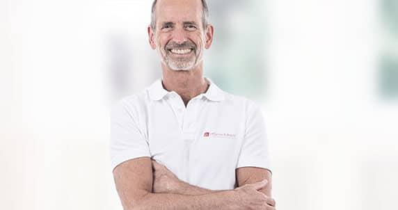 Roland Liebscher-Bracht lächelt, von Kopf bis Bauch angezeigt. Im Hintergrund unscharfe Gegenstände