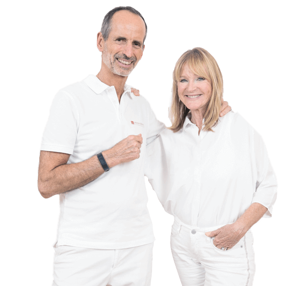 Roland Liebscher-Bracht und Petra Bracht sind ganz in weiß gekleidet und umarmen sich. Dabei lächeln sie in die Kamera.