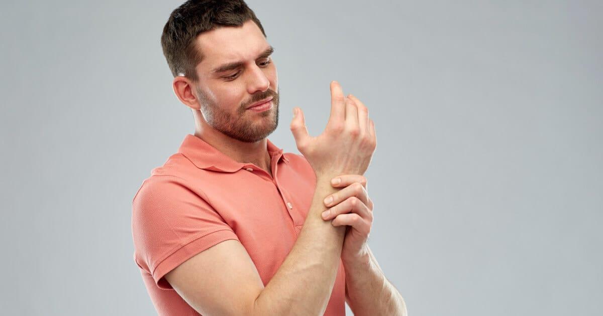 Ein Mann hält sich sein schmerzendes Handgelenk