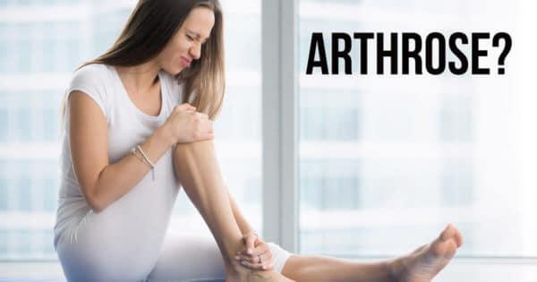 Eine Frau hält sich ihr Knie vor Arthrose-Schmerzen