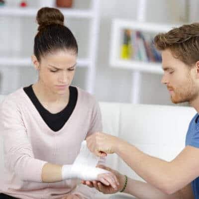 Eine junge Frau bekommt ihr Handgelenk verbunden