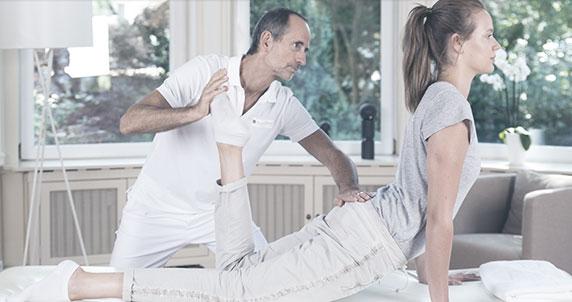 Ein junge Frau ist auf einer Behandlungsliege und stützt sich auf ihren Arm ab, während ihre Beine abliegen. dadurch ist Sie im Hohlkreuz. Ein Mann (Roland Liebscher - Bracht) steht konzentriert hinter ihr, beugt ihr linkes Bein nach oben und hält den Po nach unten.