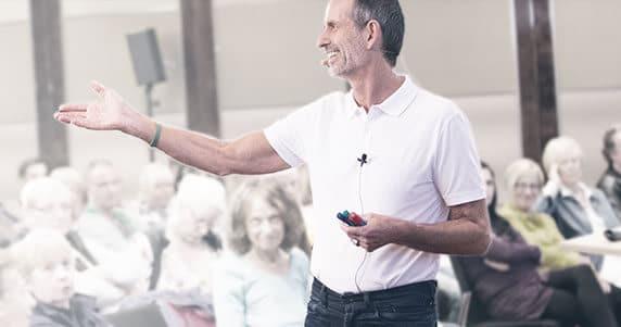Auf diesem Bild sieht man Roland von Liebscher & Bracht . Er hält drei Stifte in der linken Hand mit den Farben Rot,Schwarz,Grün. Mit der rechten Hand zeigt er auf sitzende Personen die ihm zuhören. Roland ist ausgestattet mit einem Mikrofon und trägt ein weißes T-Shirt.