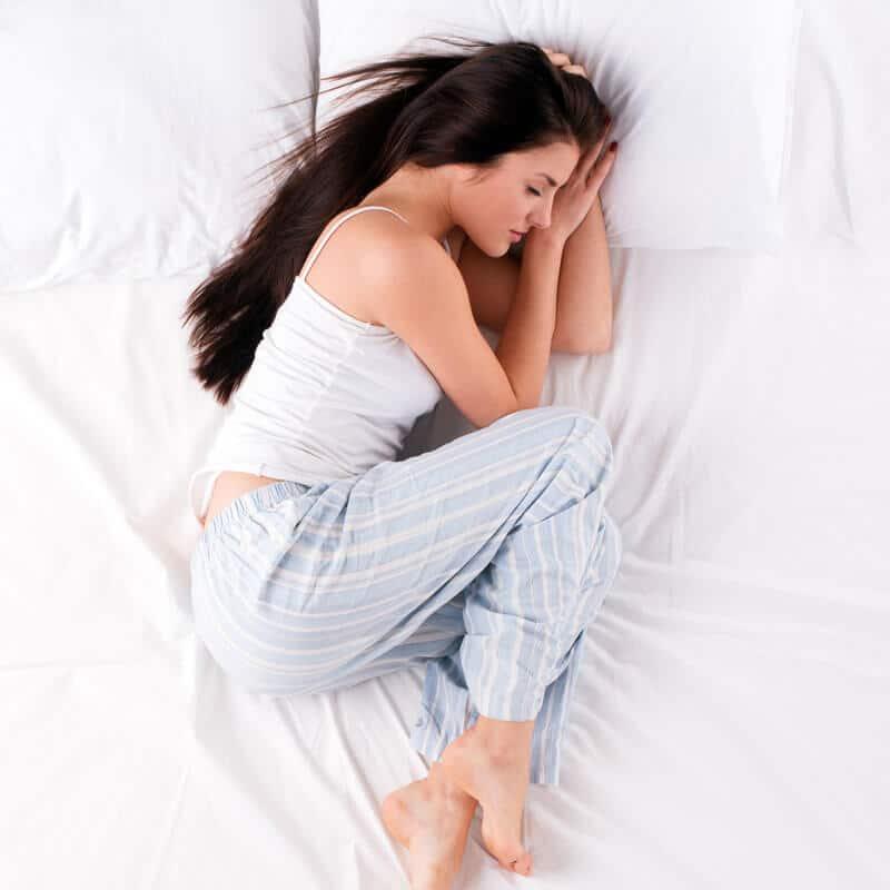 Eine Frau schläft in der Embryonalhaltung mit angezogenen Beinen