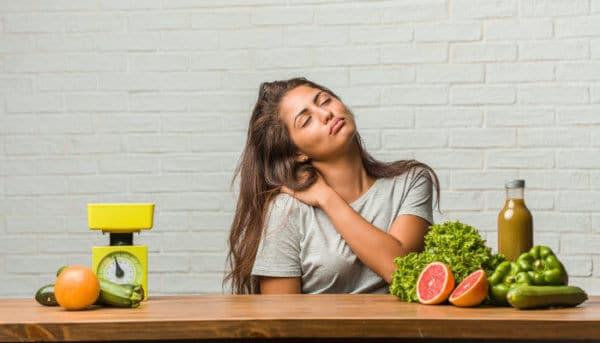 Frau sitzt mit Nackenschmerzen am Tisch nicht Obst und Gemüse