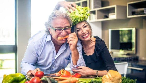 Älteres Ehepaar scherzt mit Gemüse in der Küche