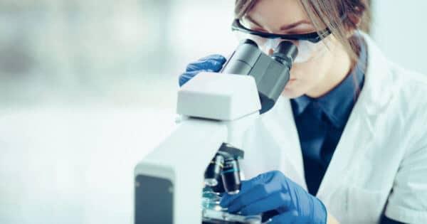 Eine Frau trägt einen weißen Kittel und sie hat blaue Handschuhe an. Sie hat eine Schutzbrille aufgesetzt und ihre Haare zusammengebunden. Die Frau schaut in einem Mikroskop . Der Hintergrund ist sehr Hell fast weiß.