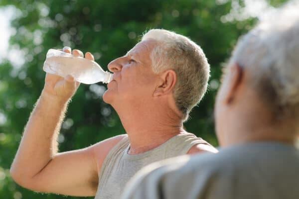 Älterer Mann trinkt Wasser nach dem Sport