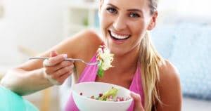 Eine sportliche Frau isst freudig eine Schüssel Salat