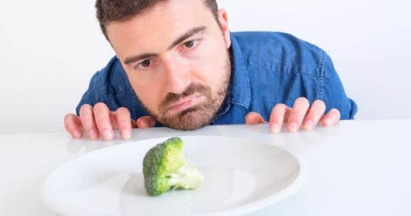 Ein Mann betrachtet traurig ein Brokkoli-Röschen auf einem Teller