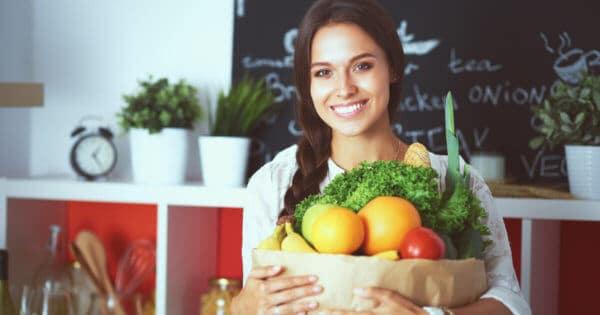 Eine Vegetarierin mit einem Korb voll Obst und Gemüse