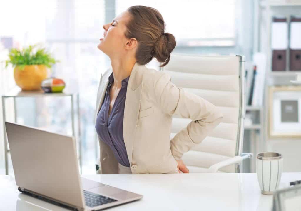 Eine Frau hat ein Piriformis-Syndrom, das durch zu langes Sitzen im Büro ausgelöst wurde.
