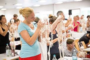 Es sind mehrere Personen zu sehen, die alle Leute auf einem Skelett rote Punkte aufmalen.