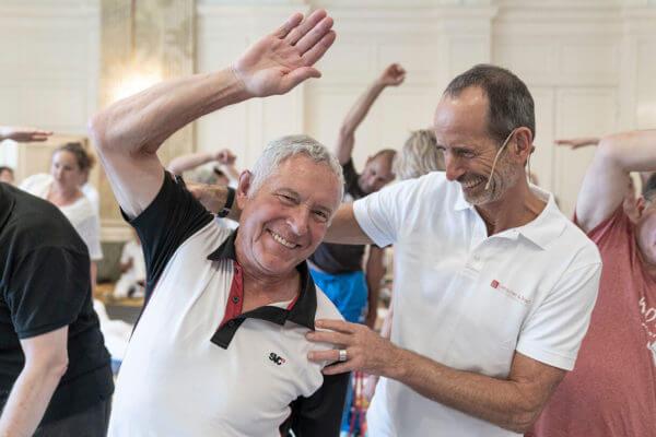 Der linke Mann beugt lächelnd seinen rechten Arm über den Kopf und wird rechts von einem Mann in Weiß (Roland Liebscher-Bracht) lächelnd angeleitet