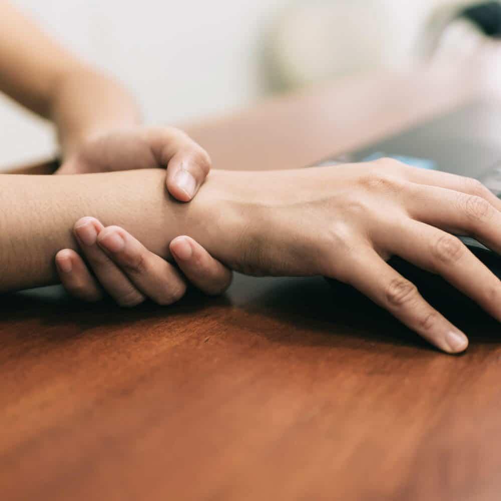 Frau umgreift mit einer Hand das Handgelenk der anderen Hand. Mit dieser bedient sie eine Maus.