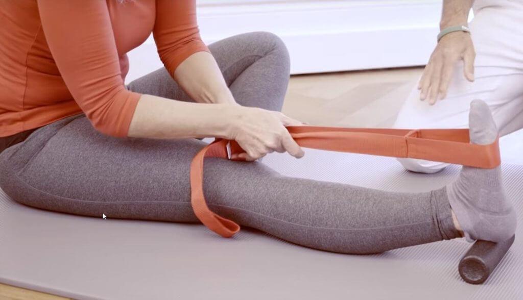 Patientin führt Engpassdehnung mit Übungs-Schlaufe gegen Meniskus-Schmerzen durch