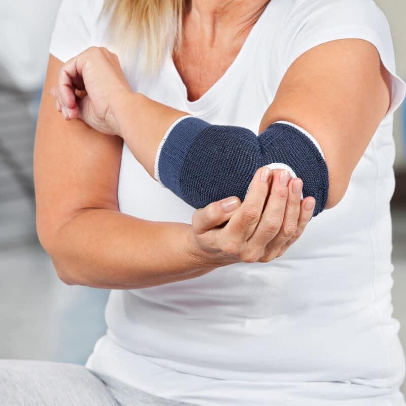Eine Frau mit einer blauen Bandage an ihrem hypermobilen Ellenbogen