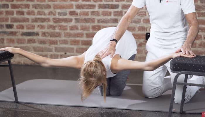 Eine Patientin kniet zwischen zwei Stühlen, hat ihre Hände darauf abgelegt und lässt ihren Brustkorb heruntersinken