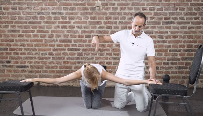 Eine Patientin bereitet die Dehnung ihrer Brustmuskulatur vor, indem sie mit ausgestreckten Armen zwischen zwei Stühlen kniet und ihre Hände darauf ablegt