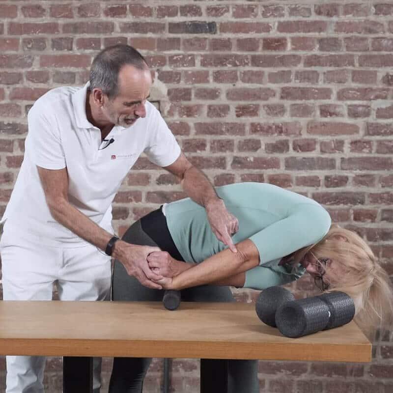 Dehnübung des hinteren Unterarms zur Behandlung eines Tennisellenbogens, bei der eine Patientin, angeleitet von Roland Liebscher-Bracht, mit dem linken Arm ihren rechten Unterarm dehnt und diesen dabei bis zur Außenseite des Ellenbogens mit der Mini-Faszienrolle abrollt